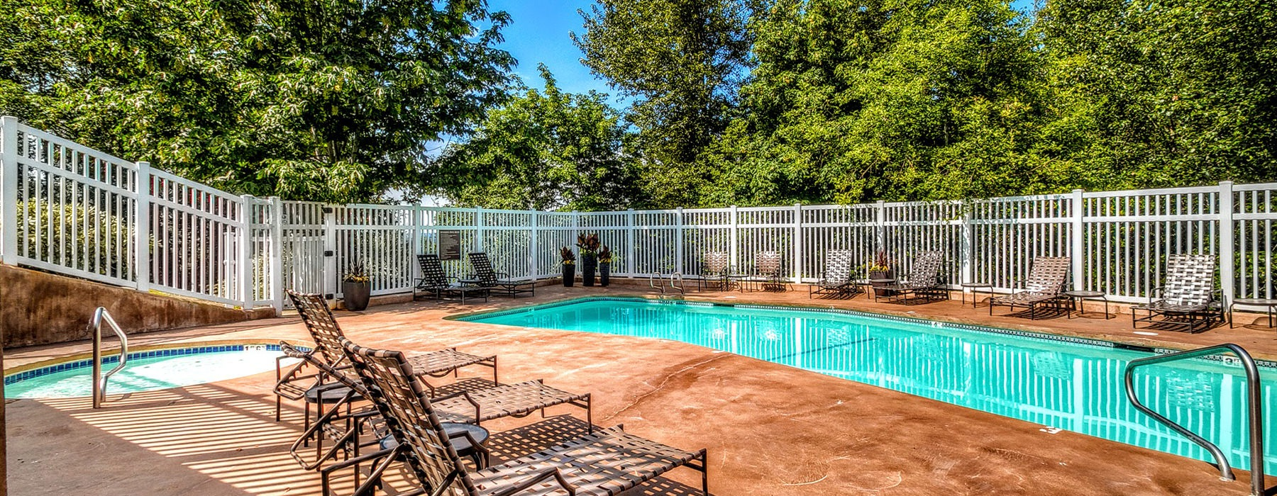 Fenced in pool and hot tub area with lounge chairs